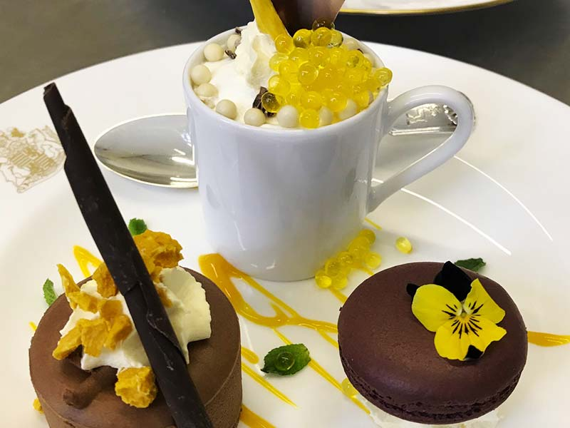 Mini chocolate torte, white chocolate mousse and a dark chocolate macaroon with mango cream